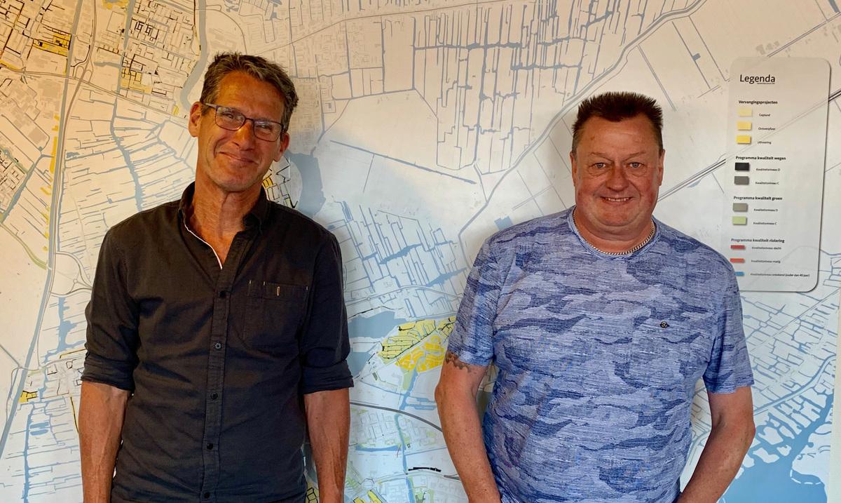 Op deze foto zie je twee mannen met daarachter een plattegrond als poster