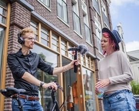Foto van journalist Robin de Wever die een inwoner interviewst voor zijn podcastserie Het Zaanse Avontuur.